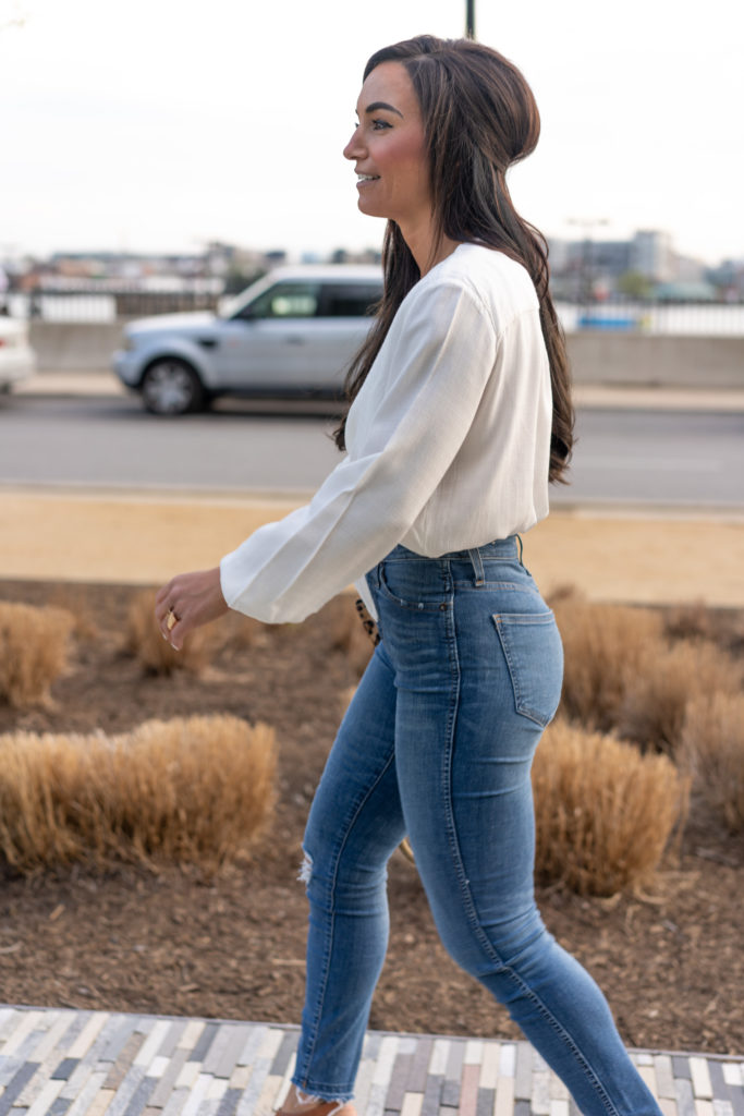 Model in Blue Jeans and white tie front shirt.