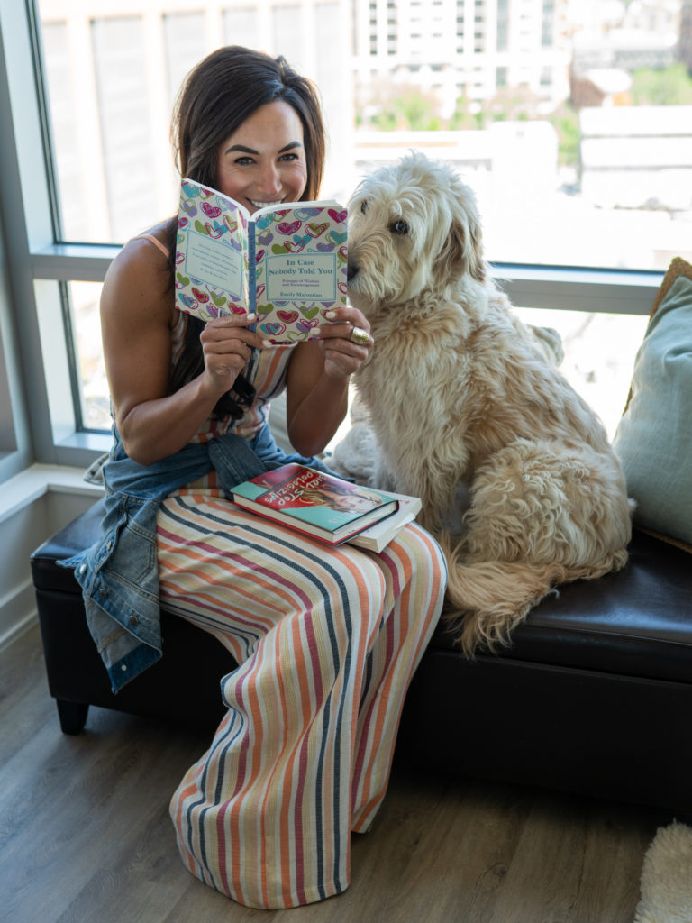 Model sitting down to read a book with her dog.