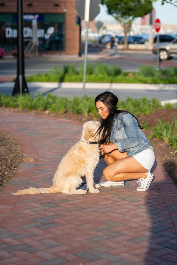 Female model with her dog wearing a jean jacket.