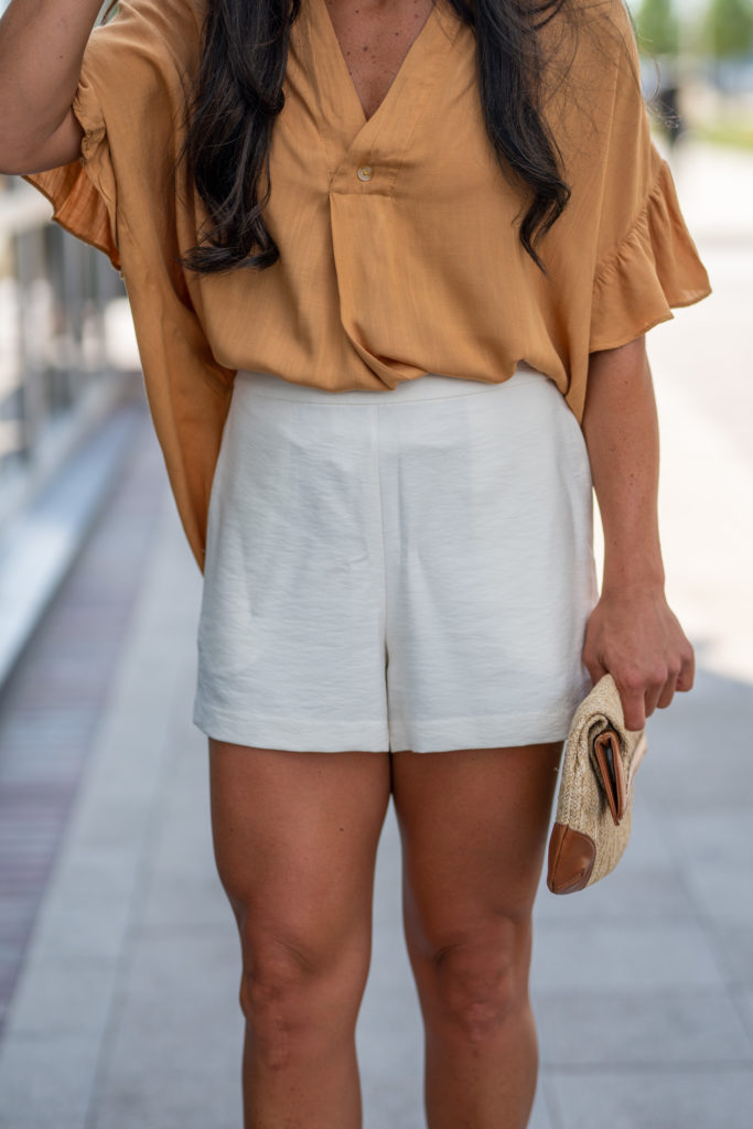 Model wearing white shorts in summer.