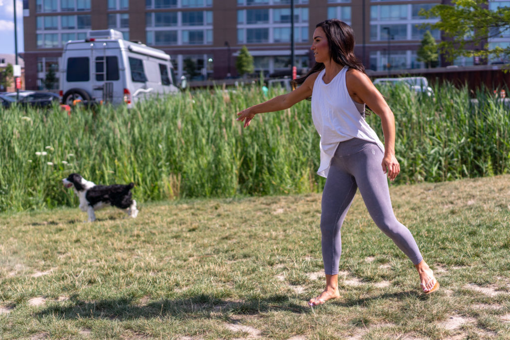 Model playing frisbee with dogs in a field.