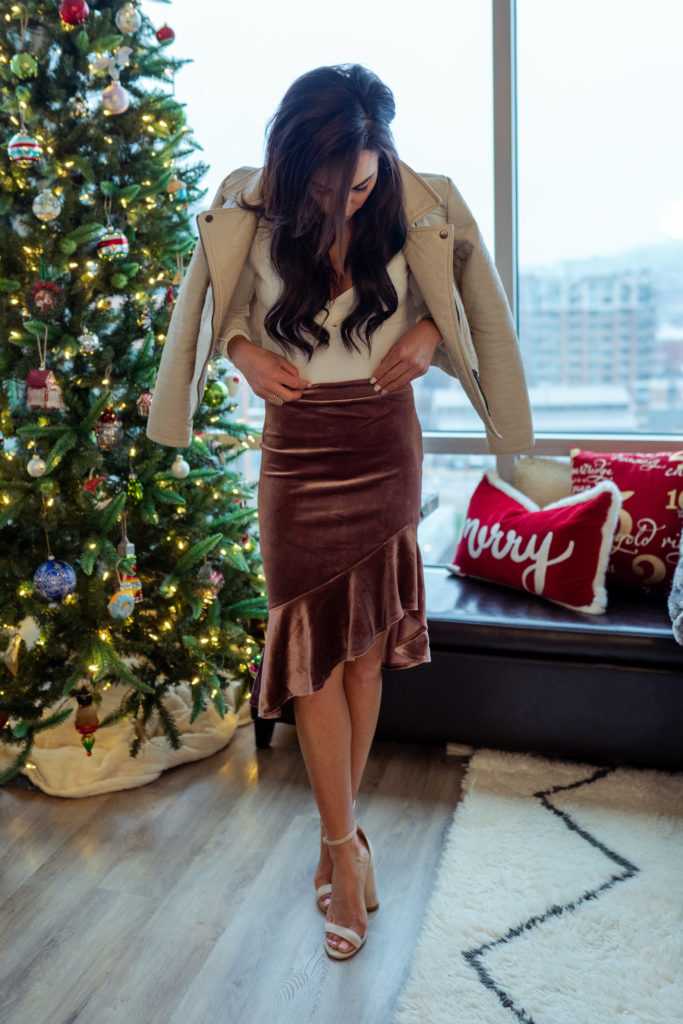 Holiday outfit on model posing by tree.