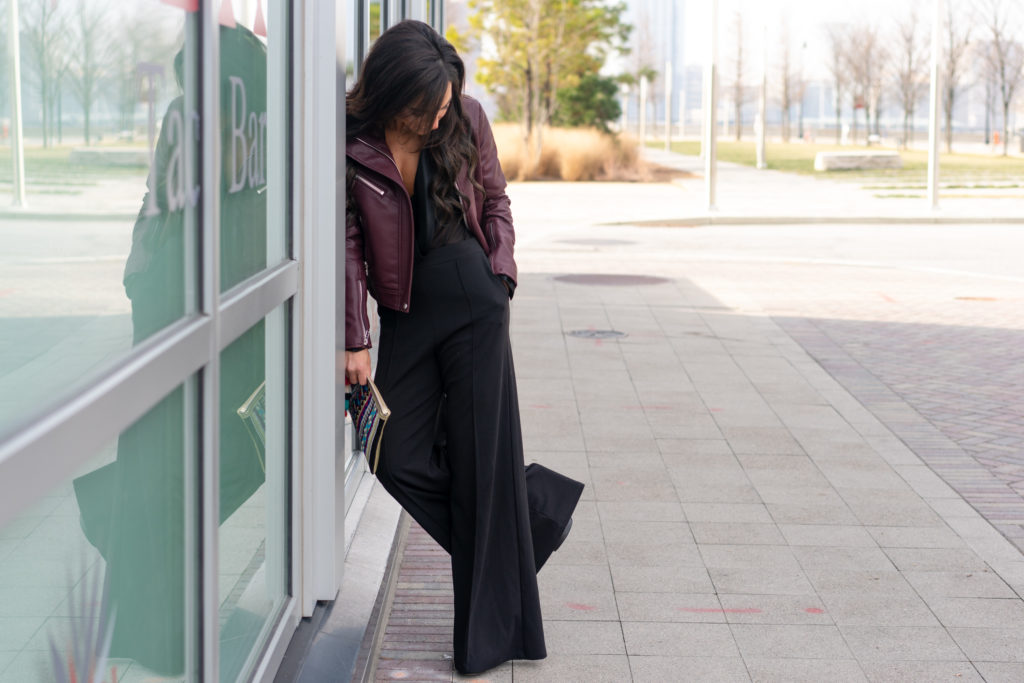 Model wearing wide legged pants and leather jacket.