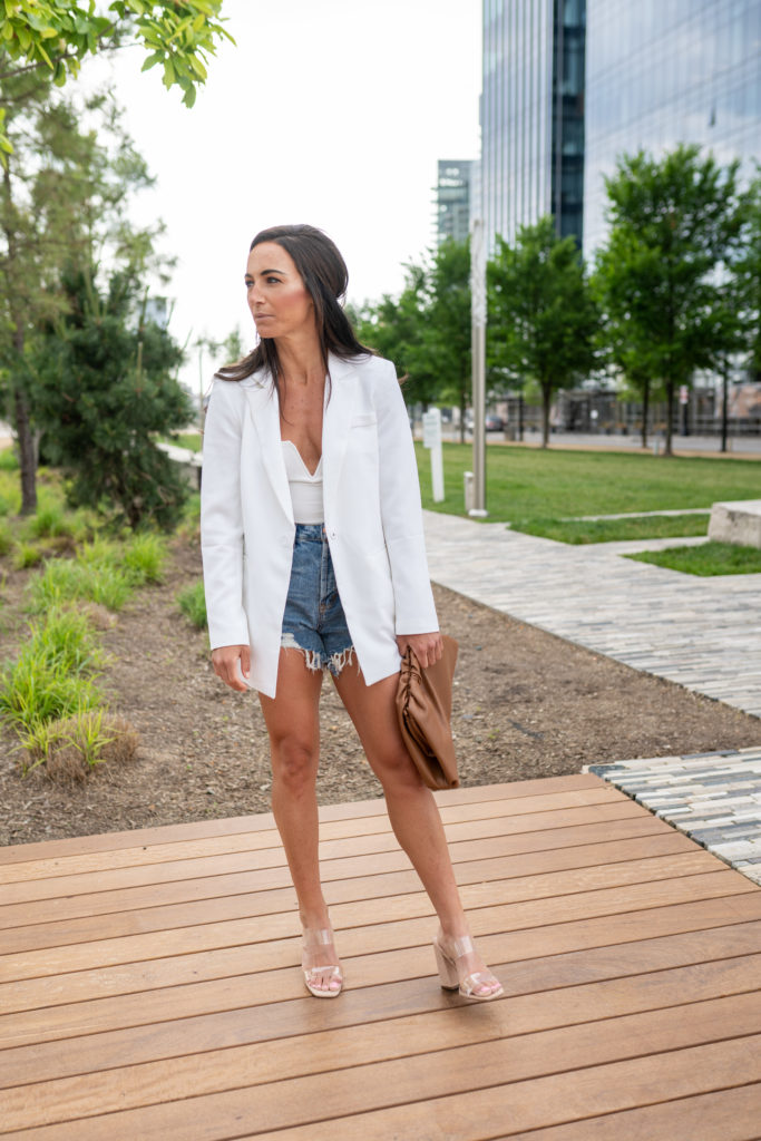 Model wearing white blazer with clutch and jean shorts.