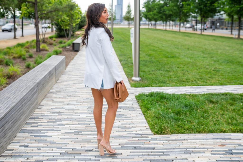 Model wearing white blazer with clutch.